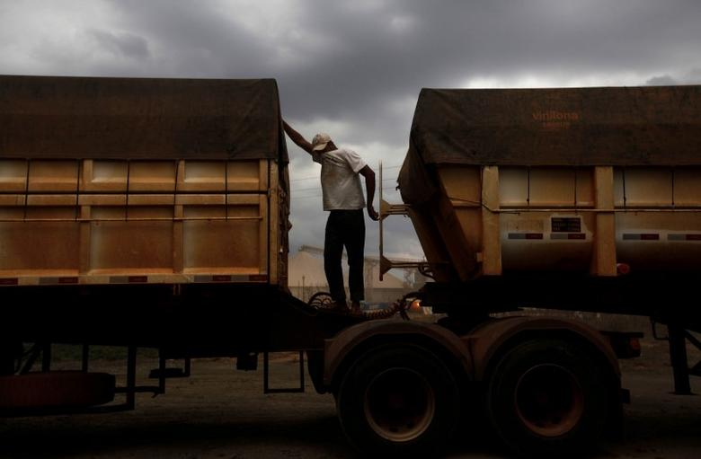 A Brazilian truck driver covers his face to protect himself from dust as he waits to unload his cargo of cereal grain at the rail terminal of America Latina Logistica (ALL), along highway BR-364 in Alto de Araguaia, Mato Grosso state September 24, 2012.   REUTERS/Nacho Doce/File Photo