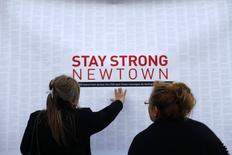 A woman touches a printout of messages from teenagers around the United States at a memorial for the victims of the Sandy Hook Elementary School shooting in Newtown, Connecticut December 18, 2012. REUTERS/Joshua Lott