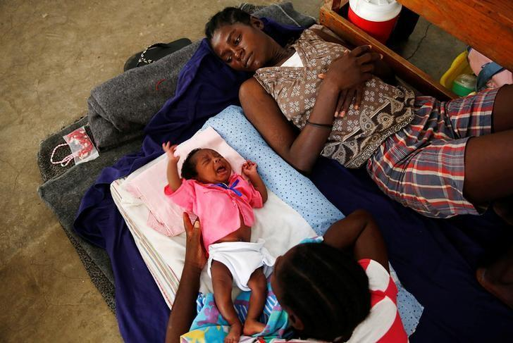 Women and a child rest at a shelter set up at a school after Hurricane Matthew passes in Jeremie, Haiti, October 8, 2016. REUTERS/Carlos Garcia Rawlins