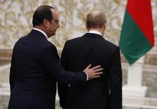 """Президент Франции Франсуа Олланд и российский лидер Владимир Путин на встрече в Минске 11 февраля 2015 года. Французский президент не уверен, что увидится с российским лидером Владимиром Путиным, планирующим навестить Париж 19 октября, и осуждает его """"неприемлемую"""" поддержку авиаударов в Сирии, которые, по словам Олланда, заслуживают трибунала в Гааге. REUTERS/Grigory Dukor"""