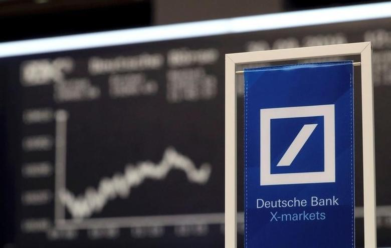A Deutsche Bank banner is pictured in front of the German share price index, DAX board, at the stock exchange in Frankfurt, Germany September 30, 2016. REUTERS/Kai Pfaffenbach/File Photo