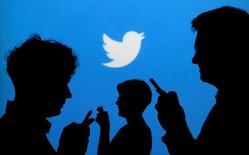 Люди со смартфонами на фоне логотипа Twitter. Акции Twitter Inc подешевели более чем на 14 процентов в начале торгов понедельника после сообщения Bloomberg в выходные о том, что основные потенциальные покупатели, включая Salesforce.com Inc, потеряли интерес к приобретению сервиса микроблогов.  REUTERS/Kacper Pempel/Illustration/File Photo