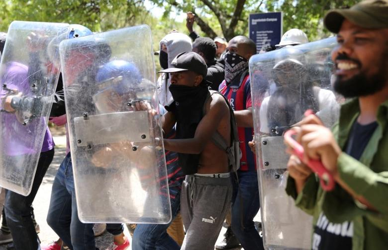 Students demanding free education use shields belonging to private security during clashes with police officers at the Johannesburg's University of the Witwatersrand, South Africa, October 11,2016. REUTERS/Siphiwe Sibeko