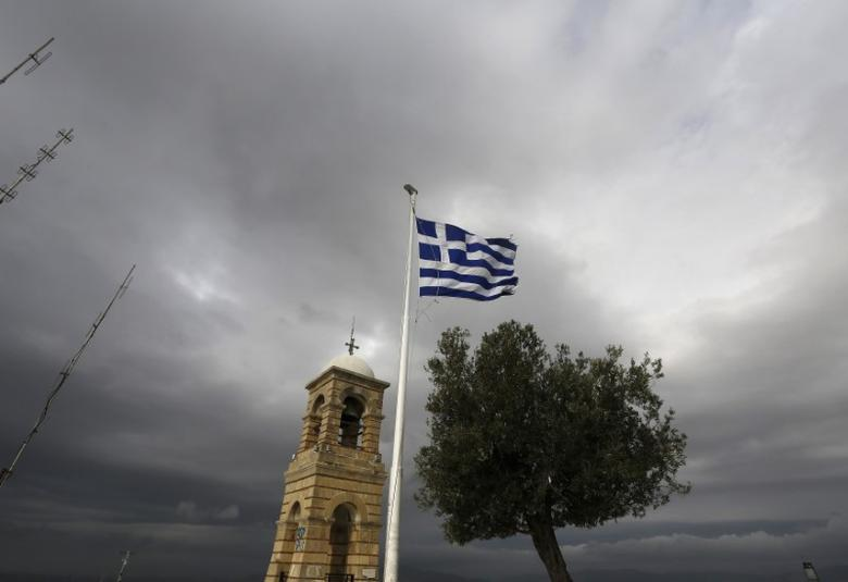 A Greek flag flutters between Saint George's bell tower and an olive tree atop the Lycabettus hill March 6, 2015. REUTERS/Yannis Behrakis