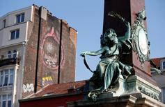 A sculpture is seen near an explicit graffiti painted on the side of a building in central Brussels, Belgium, October 11, 2016. REUTERS/Francois Lenoir