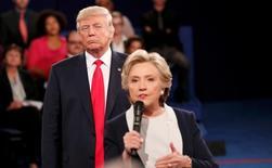 Кандидат в президенты США от республиканцев Дональд Трамп слушает конкурента от демократов Хиллари Клинтон на теледебатах в Сент-Луисе, штат Миссури, 9 октября 2016 года. Трамп еще отстал от Клинтон, теперь на 8 процентных пунктов, показал новый опрос потенциальных избирателей, проведенный Рейтер и социологами Ipsos. REUTERS/Rick Wilking