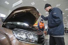 Покупатель изучает автомобиль Лада в дилерском магазине Автоваза в Москве. Акционеры Автоваза одобрили увеличение уставного капитала крупнейшего российского автопроизводителя на 3,281 миллиарда акций номинальной стоимостью 5 рублей, сообщила компания в среду.  REUTERS/Maxim Shemetov