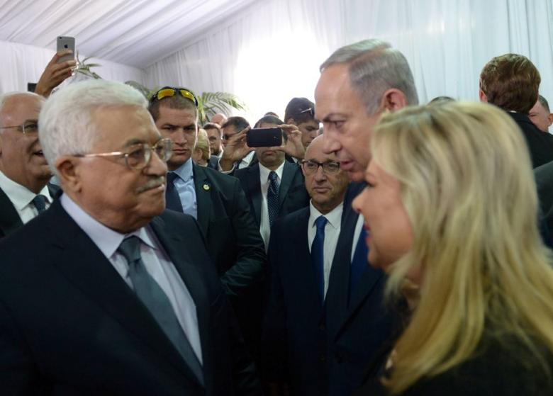 Israeli Prime Minister Benjamin Netanyahu and his wife Sara speak to Palestinian President Mahmoud Abbas (L) during the funeral of former Israeli President Shimon Peres in Jerusalem September 30, 2016.  Amos Ben Gershom/Government Press Office (GPO)/Handout via REUTERS