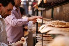Мужчины раскладывают лепешки, чтобы их охладить. Дамаск, 17 сентября 2016 года. Сирийское государственное агентство по закупке зерна Hoboob купило один миллион тонн российской пшеницы по 150 евро за тонну на условиях CFR, сказал Рейтер источник в правительстве Сирии, знакомый с ситуацией. REUTERS/Omar Sanadiki