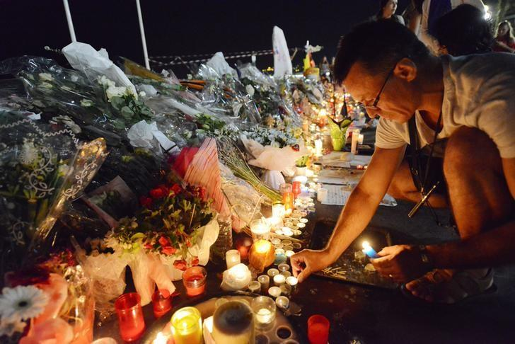 A man places candles near flowers that were left in tribute at makeshift memorials to the victims of the truck attack along the Promenade des Anglais in Nice, France, July 18, 2016.  REUTERS/Jean-Pierre Amet/File Photo