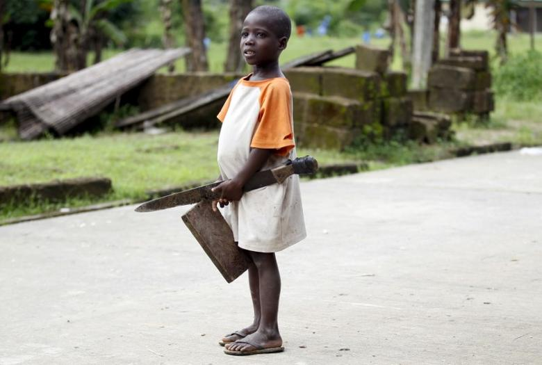 A boy holding a cutlass stands in a street in Ikarama village on the outskirts of the Bayelsa state capital, Yenagoa, in Nigeria's delta region October 8, 2015. REUTERS/Akintunde Akinleye