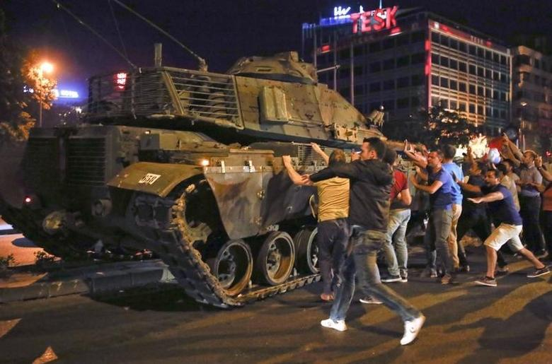 People react near a military vehicle during an attempted coup in Ankara, Turkey, July 16, 2016. REUTERS/Tumay Berkin/Files