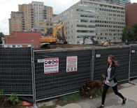 A woman passes a condominium construction site on what used to be a neighborhood of single family homes in Toronto, Ontario, Canada October 3, 2016. REUTERS/Chris Helgren