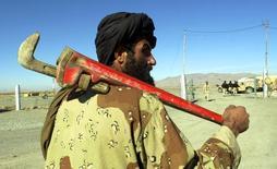 Союзник американских вооруженных сил в Афганистане Махмад Садек несет большой разводной ключ в международном аэропорту Кандагара 19 декабря 2001 года. Десятилетия обсуждаемый проект 1.814-километрового газопровода ТАПИ - из Туркмении в Пакистан и Индию через неспокойный Афганистан - ищет финансирование, и на ноябрь запланировано роудшоу для инвесторов, сообщил в пятницу пакистанский чиновник. REUTERS/Dave Martin