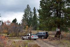 RCMP vehicles block the road leading to the crash site of a corporate jet, in which former Alberta Premier Jim Prentice died, in a forested area near Winfield, British Columbia, Canada October 14, 2016.  REUTERS/Dennis Owen