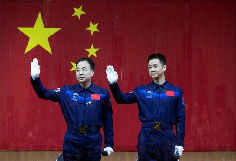Chinese astronauts Jing Haipeng (L) and Chen Dong wave at a news conference before China launches the Shenzhou 11 manned spacecraft, in Jiuquan, China, October 16, 2016. China Daily/via REUTERS