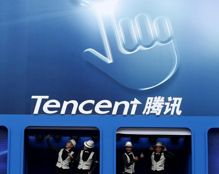 Dancers perform underneath the logo of Tencent at the Global Mobile Internet Conference in Beijing May 6, 2014. REUTERS/Kim Kyung-Hoon/Files