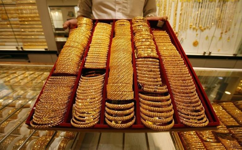 A salesman displays a tray of gold bangles for the camera at a jewellery shop in Singapore October 7, 2009. REUTERS/Vivek Prakash/Files