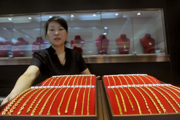 A sales woman displays a gold bracelets as she poses for pictures at a jewellery shop in Lin'an, Zhejiang province, China, July 29, 2015. REUTERS/China Daily/Files