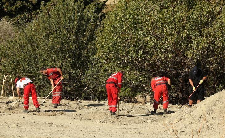 A South Yorkshire police officer (R) and members of the Greek rescue service (in red uniforms) investigate the ground while excavating a site for Ben Needham, a 21 month old British toddler who went missing in 1991, on the island of Kos, Greece, September 28, 2016. REUTERS/Vassilis Triandafyllou/Files