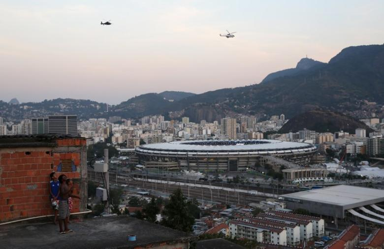 Rio de Janeiro, Brazil - 05/08/2016. Residents look down on the Maracana stadium from the Mangueira favela, or slum as helicopters fly overhead.  REUTERS/Pilar Olivares