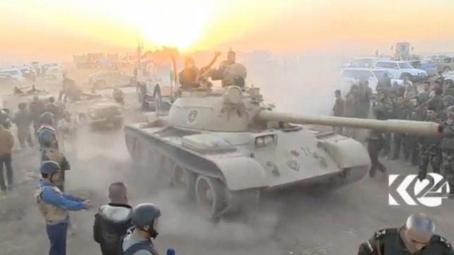 Tanks move past soldiers in military fatigues as the sun begins to set east of Mosul, where the Iraqi government launched a U.S.-backed offensive to drive Islamic State from the northern city, in this still image taken from video released October 17, 2016.  RUDAW via REUTERS VIDEO NEWS