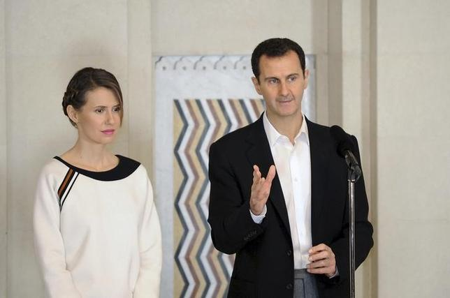 Syria's President Bashar al-Assad stands next to his wife Asma, as he addresses injured soldiers and their mothers during a celebration marking Syrian Mother's Day in Damascus, in this handout picture provided by SANA on March 21, 2016. REUTERS/SANA/Handout via Reuters/File Photo