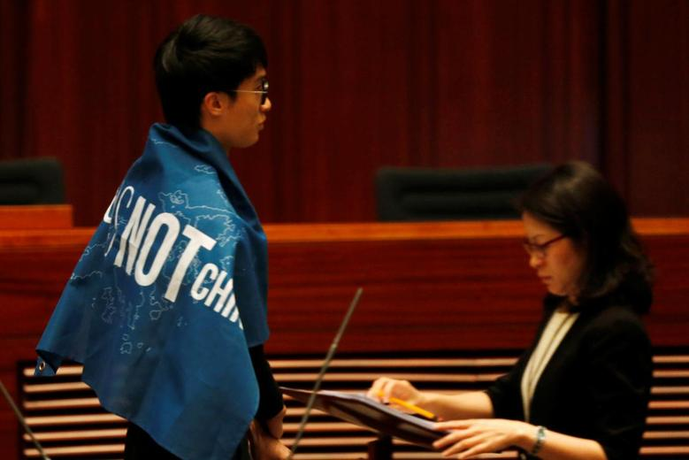 Newly-elected lawmaker Baggio Leung wears a banner ''Hong Kong is not China'' while taking oath at the Legislative Council. REUTERS/Bobby Yip