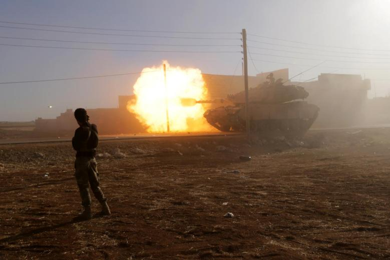 A rebel fighter stands near a Turkish tank as it fires towards Guzhe village, northern Aleppo countryside, Syria. REUTERS/Khalil Ashawi