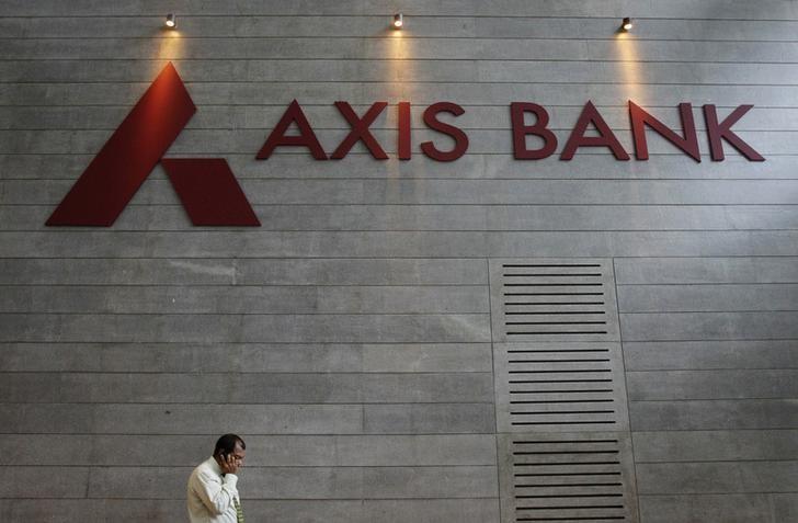 An employee speaks on his mobile phone as he walks inside Axis Bank's corporate headquarters in Mumbai July 17, 2012. s.  REUTERS/Vivek Prakash