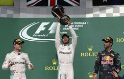 Formula One F1 - U.S. Grand Prix - Circuit of the Americas, Austin, Texas, U.S., 23/10/16. Mercedes' Lewis Hamilton of Britain raises his victory trophy as second placed finisher and teammate Nico Rosberg of Germany (L) and third placed Red Bull's Daniel Ricciardo of Australia (R) look on during the victory ceremony.    REUTERS/Adrees Latif