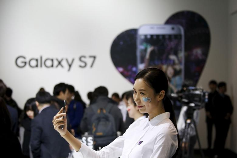 A model poses for photographs with Samsung Electronics' new smartphone Galaxy S7 during its launching ceremony in Seoul, South Korea, March 10, 2016.  REUTERS/Kim Hong-Ji - RTSA41M