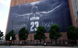 A woman on the sidewalk is dwarfed by a giant picture of NBA basketball Cleveland Cavaliers player LeBron James in downtown Cleveland across the street from the Republican National Convention July 13, 2016.  REUTERS/Rick Wilking