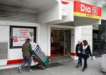La cadena de distribución DIA caía el martes en bolsa más de un 7 por ciento, después de presentar unos resultados en línea con el mercado pero con unos niveles de deuda que despertaron la preocupación de los inversores. En la imagen, gente camina delante de un supermercado de DIA en Madrid, el 23 de febrero de 2015.  REUTERS/Juan Medina
