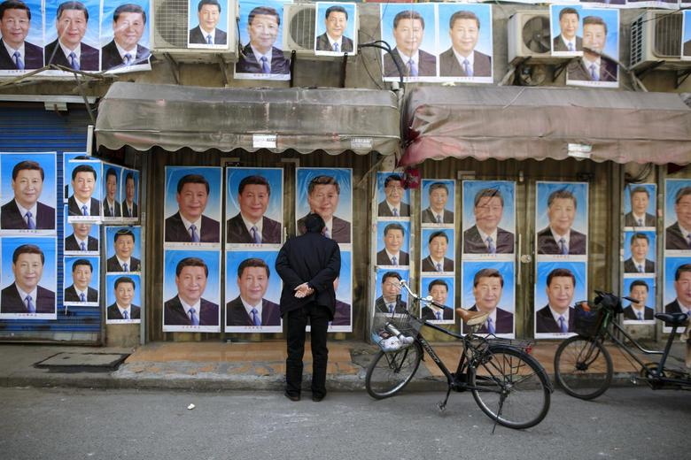 A man looks at a building covered in posters of Chinese President Xi Jinping in Shanghai, China, March 26, 2016. REUTERS/Aly Song/File Photo