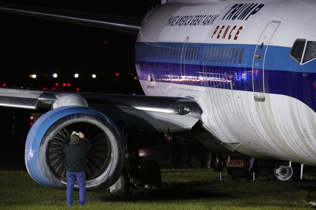 Mike Pence's campaign airplane sits partially on the tarmac and the grass  after sliding off the runway while landing at LaGuardia airport, Thursday,  ...