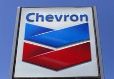 Знак на автозаправке Chevron в Калифорнии. Chevron Corp в пятницу отчиталась о снижении квартальной прибыли, которая в то же время превзошла прогнозы аналитиков, поскольку сокращение расходов в подразделении нефтедобычи в США, помогло смягчить негативные последствия снижения цен на нефть.   REUTERS/Mike Blake/File Photo