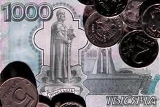 Рублевые монеты и купюра. Рубль в небольшом минусе утром понедельника на фоне текущей отрицательной динамики нефти, а также после уплаты октябрьских налогов, хотя участники рынка отмечают более-менее равномерные продажи экспортной валютной выручки в течение всего календарного месяца, из-за чего негативный эффект от завершения налогового периода может быть ограничен.  REUTERS/Maxim Zmeyev/Illustration