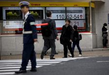 Electronic boards show the exchange rate between Japanese yen against the U.S. dollar as a police officer (L) controls the traffic in front of a brokerage in Tokyo, Japan April 6, 2016. REUTERS/Issei Kato