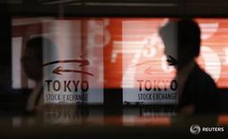 Человек проходит мимо логотипов Токийской фондовой биржи 6 февраля 2013 года. Ведущий фондовый индекс Японии Nikkei повысился в ходе волатильных торгов вторника, после того как Банк Японии, как и ожидалось, оставил денежно-кредитную политику без изменений, но рост котировок ограничили разочаровывающие прогнозы прибыли некоторых компаний. REUTERS/Toru Hanai