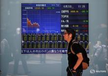 Человек проходит мимо табло с графиком движения котировок индекса Nikkei  в Токио 2 июня 2016 года. Японский индекс Nikkei просел до минимума двух недель в среду, поскольку рынки беспокоит неопределенность в отношении результатов президентских выборов в США, а рост иены усилил бегство от риска.  REUTERS/Issei Kato