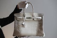Демонстрация редкой сумки Hermes перед аукционом Christie's в Париже. Французский люксовый бренд одежды и аксессуаров Hermes сообщил в четверг о небольшом ускорении роста продаж в третьем квартале финансового года - на 8,8 процента против 8,1 процента за предыдущие три месяца.   REUTERS/Christian Hartmann