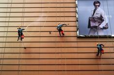 En la imagen, trabajadores limpiando el exterior de un edificio junto a un cartel en Wuxi, provincia de Jiangsu. El sector de servicios de China creció en octubre a su ritmo más alto en cuatro meses gracias a un repunte de los nuevos negocios, lo que alentó a las compañías a contratar más trabajadores, mostró un sondeo privado. REUTERS/Stringer/File Photo