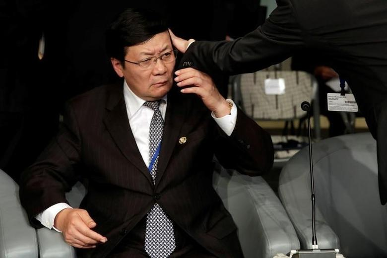 An aid adjusts a hair of Chinese Finance Minister Lou Jiwei before the Development Committee meeting during the IMF/World Bank annual meetings in Washington, U.S., October 8, 2016. REUTERS/Yuri Gripas