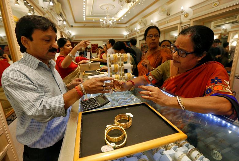A salesman shows gold bangles to a customer at a jewellery showroom during Dhanteras, a Hindu festival associated with Lakshmi, the goddess of wealth, in Kolkata, India October 28, 2016. REUTERS/Rupak De Chowdhuri/Files