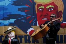 Исполнитель мексиканской народной музыки мариачи выступает рядом с карикатурой на кандидата в президенты США Дональда Трампа в Мехико 25 сентября 2016 года. Национальная валюта Мексики подорожала во вторник до двухмесячного максимума, поскольку инвесторы ставят на победу Хиллари Клинтон над Трампом. REUTERS/Carlos Jasso