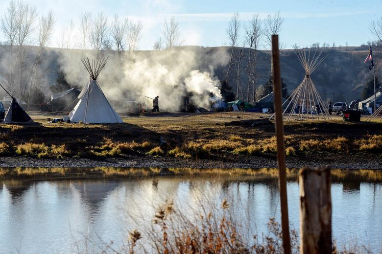 A person walks past smoke from a cooking fire at an encampment during a protest against the Dakota Access pipeline on the Standing Rock Indian Reservation near Cannon Ball, North Dakota, U.S. November 9, 2016. Stephanie Keith