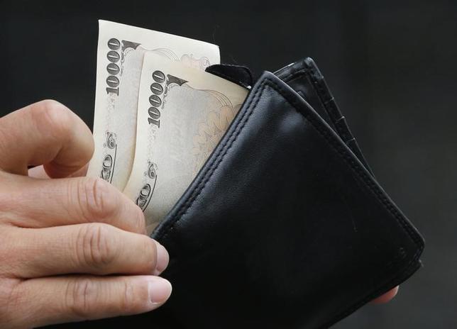 11月14日、三菱UFJフィナンシャル・グループなど大手銀行グループが発表した2016年4―9月期決算で、日銀のマイナス金利政策や海外経済の減速により、成長路線が頭打ちになっていることが鮮明になった。写真は1万円札を取り出す男性、都内で2012年11月撮影(2016年 ロイター/Kim Kyung-Hoon)