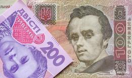Купюры валюты гривна в Киеве 6 августа 2014 года. Курс украинской гривны опустился ниже отметки 26,0 за $1 впервые за два месяца во вторник, и Нацбанк второй день подряд выступил со словесной интервенцией, назвав причиной нервозности валютного рынка политическую ситуацию в стране. REUTERS/Konstantin Chernichkin