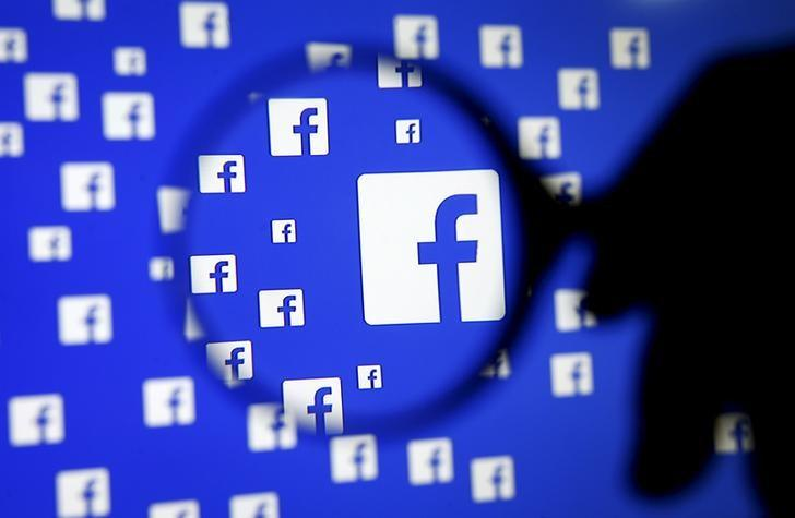 A man poses with a magnifier in front of a Facebook logo on display in this illustration taken in Sarajevo, Bosnia and Herzegovina, December 16, 2015.   REUTERS/Dado Ruvic/Illustration/File Photo   GLOBAL BUSINESS WEEK AHEAD PACKAGE - SEARCH ''BUSINESS WEEK AHEAD JULY 25'' FOR ALL IMAGES